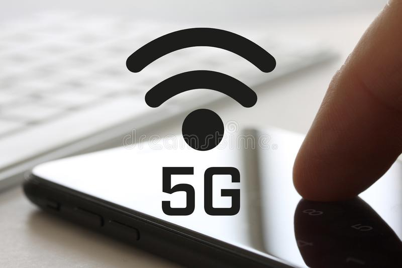 5G network concept with finger touching smartphone with screen and keybord in background. Wireless internet symbol in front of dis. Play - image royalty free stock image