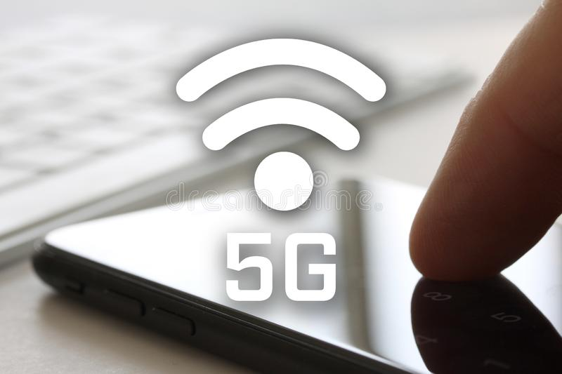 5G network concept with finger touching smartphone with screen and keybord in background. Wireless internet symbol in front of dis. Play - image stock photography