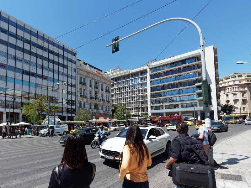G?ngare som v?ntar f?r att korsa upptagen Aten gata, Grekland royaltyfri fotografi