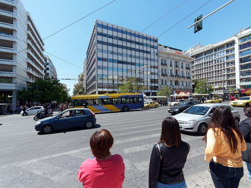 G?ngare som v?ntar f?r att korsa upptagen Aten gata, Grekland royaltyfri bild