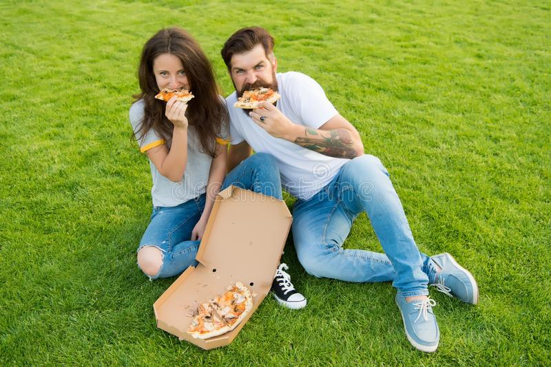 G?odni ludzie Prosty szcz??cie Nabranie posi?ek Pary łasowania pizza relaksuje na zielonym gazonie fast food dostawa brodaty m??c obraz stock