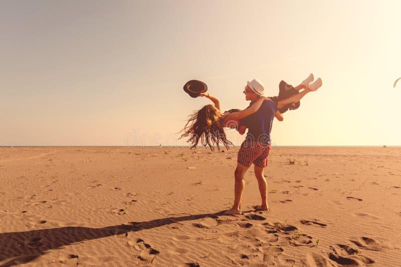 G?r den lyckliga romantiska mitt ?ldrades par som tycker om h?rlig solnedg?ng, p? stranden fotografering för bildbyråer