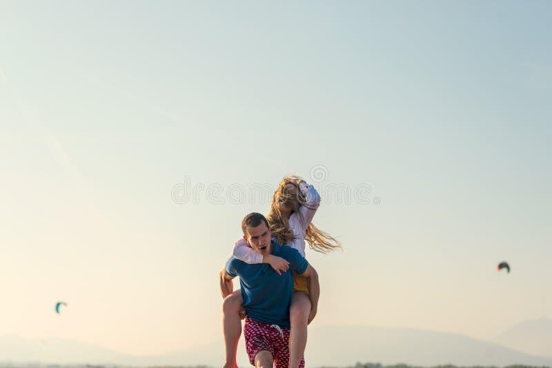 G?r den lyckliga romantiska mitt ?ldrades par som tycker om h?rlig solnedg?ng, p? stranden arkivbilder