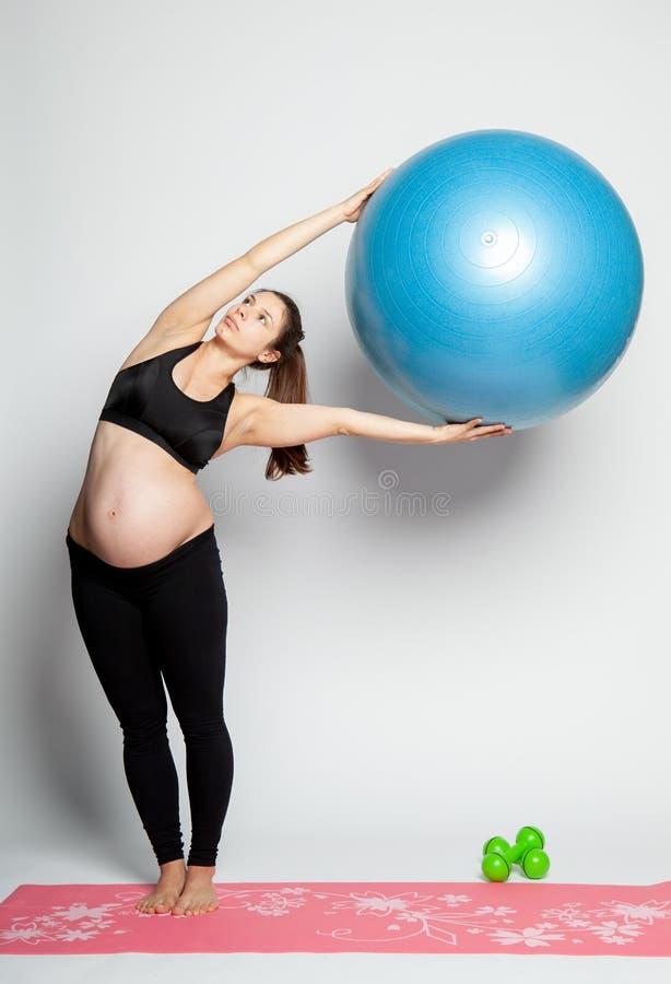 g?ra gymnastikgravid kvinnabarn arkivfoto