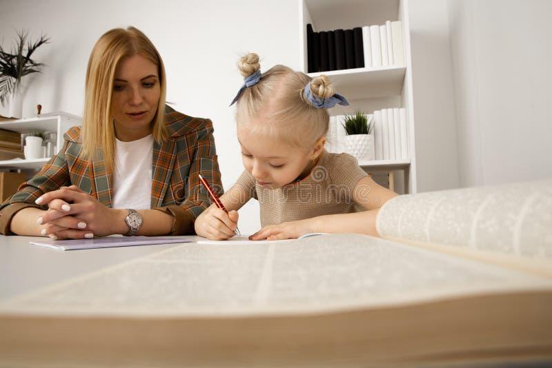 G?ra uppgifter och att studera begrepp Barnvakt med flickahandstill?xa arkivfoto