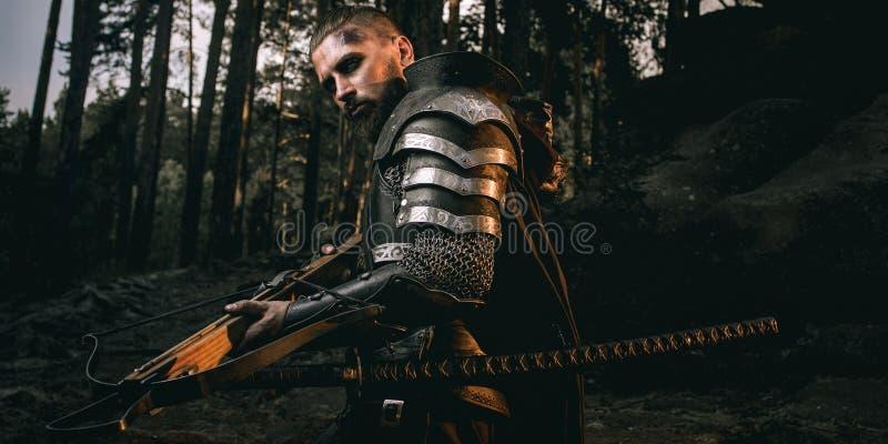G?tascarfaceriddare i harnesk med sv?rdet och armborst i skogen royaltyfri bild