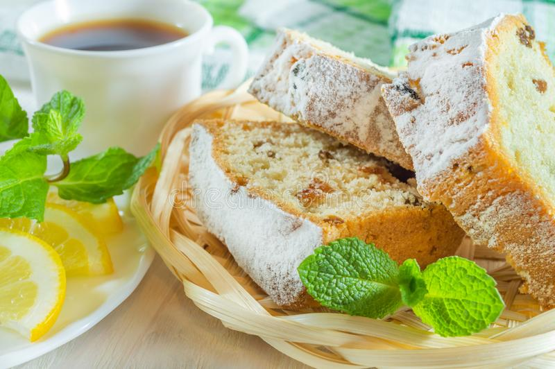 G?teau d?coup? en tranches de biscuit, une tasse de th?, tranches de citron et feuilles en bon ?tat Petit d?jeuner ou dessert d?l photographie stock
