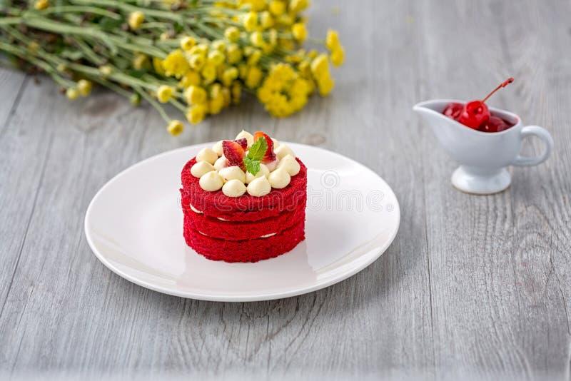 G?teau rouge tha?landais G?teau rouge de velours Biscuits d?cor?s du g?teau rouge sur la table et la fleur en bois fraises moring images stock