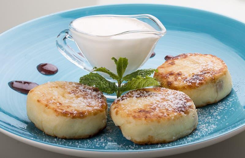 G?teaux au fromage de petit d?jeuner avec la cr?me sure d'un plat bleu photo stock