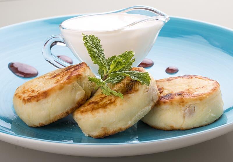 G?teaux au fromage de petit d?jeuner avec la cr?me sure d'un plat bleu image libre de droits