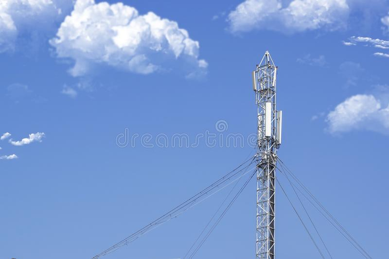 5G technology and telecommunication antenna tower against a blue sky with some clouds. Empty copy space. royalty free stock image
