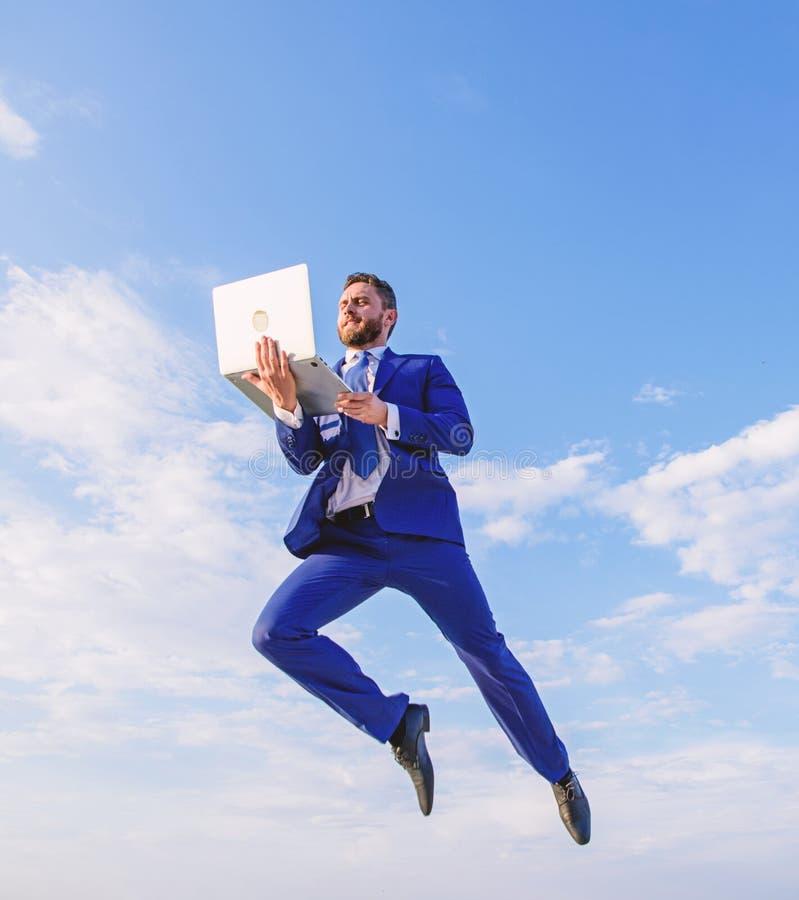 G?ttlicher Manager Gesch?ftsmanngesellschaftsanzugfliege in einer Luft mit Hintergrund des blauen Himmels des Laptops Wunderbar o stockfoto