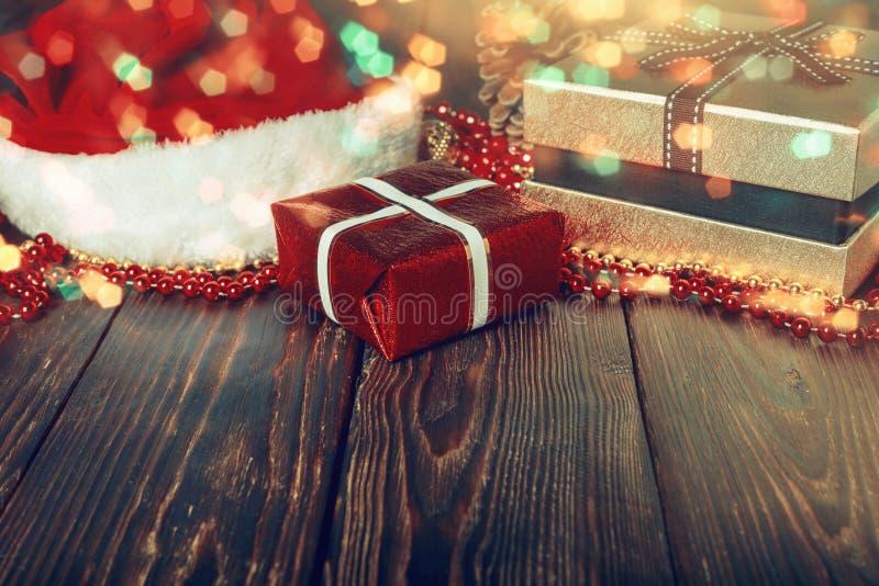 G?vaaskar med p?rlor, leksaker och den Santa Claus hatten p? ljus gl?dande bakgrund arkivfoto