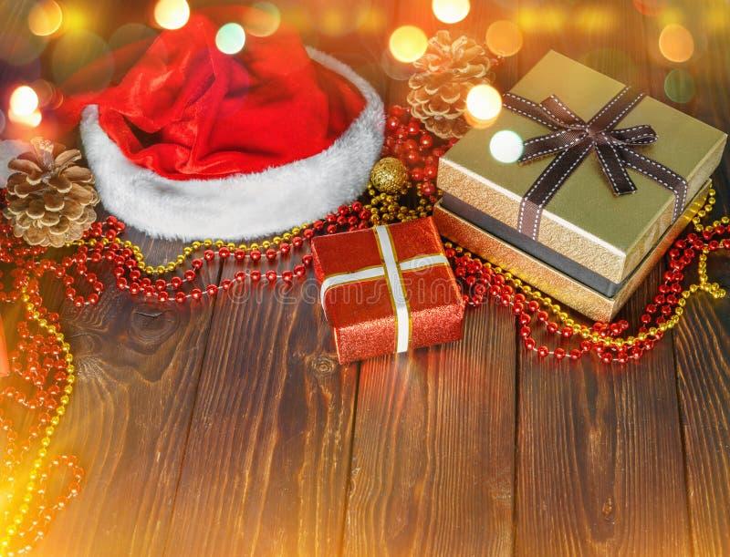 G?vaaskar med p?rlor, leksaker och den Santa Claus hatten p? ljus gl?dande bakgrund royaltyfri foto