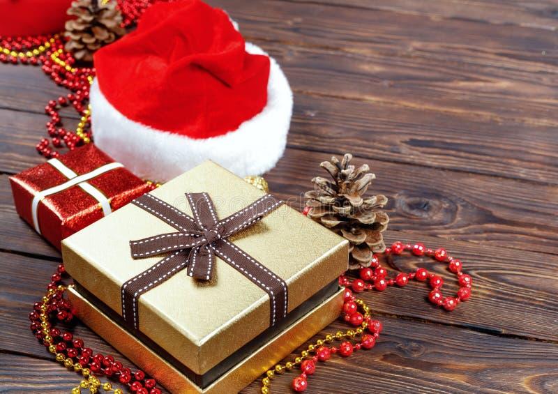 G?vaaskar med p?rlor, leksaker och den Santa Claus hatten p? tappningtr?tabellen fotografering för bildbyråer