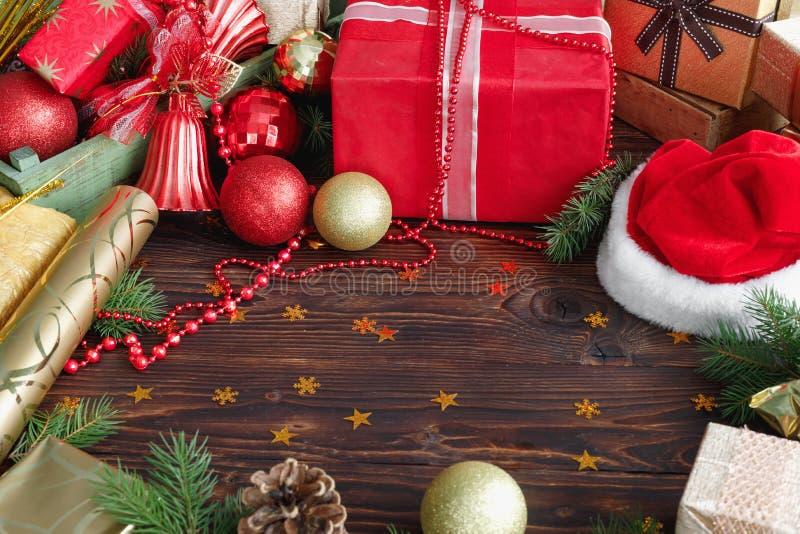 G?vaaskar med p?rlor, leksaker och den Santa Claus hatten p? tappningtr?tabellen arkivbild
