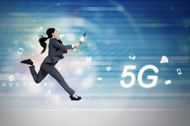 5G van de netwerksymbool en vrouw looppas met laptop stock afbeeldingen