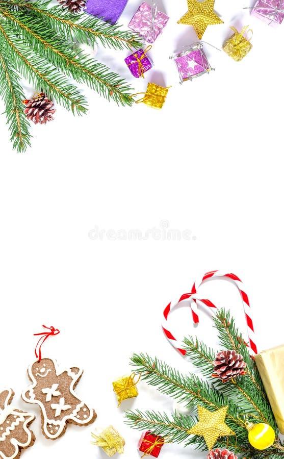 Gałąź choinka z piłkami, jedlinowymi rożkami, tradycyjnymi cukierkami i pudełkami z prezentami odizolowywającymi na białym tle, obraz stock