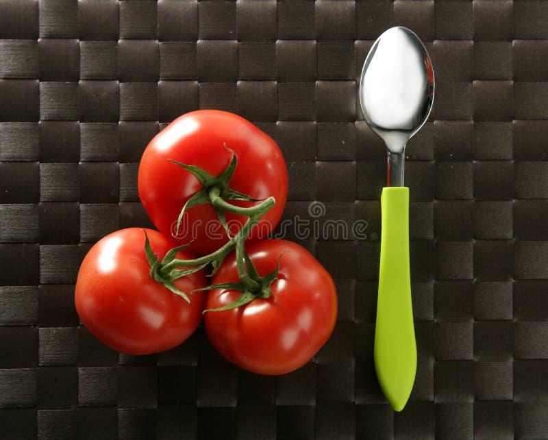 gałęziaści zieleni czerwieni łyżki trzy pomidory fotografia royalty free