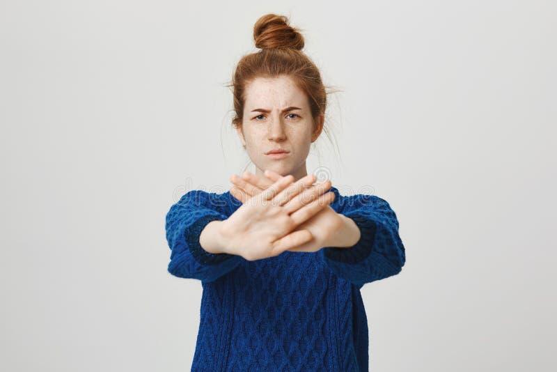 Ga weg en kom niet dichter Studioschot van ongerust gemaakt en niet bevallen aantrekkelijk gembermeisje in sweater die handen tre stock afbeelding