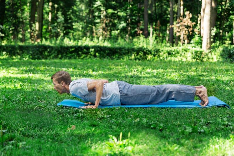 Gaat de Oung aantrekkelijke mens binnen voor sporten of de yoga op het gazon in het park, doet de plank royalty-vrije stock afbeeldingen