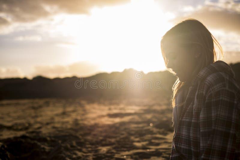 Gaat zitten de blonde jonge vrouw op het strand met zon backlight stock afbeelding