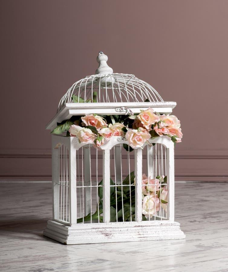 Gabbia di legno bianca con i fiori per la decorazione immagini stock