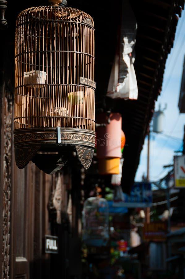 Gabbia per uccelli in piccola via asiatica fotografia stock