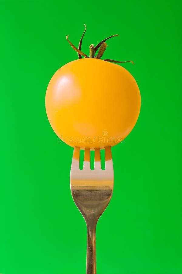 Gabel mit gelber Tomate stockbilder