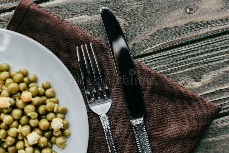 Gabel und Messer durch Platte mit Erbsen stockbilder