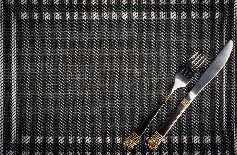Gabel und Messer mit goldenen Elementen auf einem placemat stockfoto