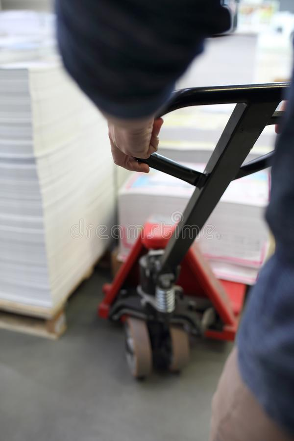 Gabelhubwagen, die Arbeitskraft lädt die Paletten auf die Laufkatze stockfotografie