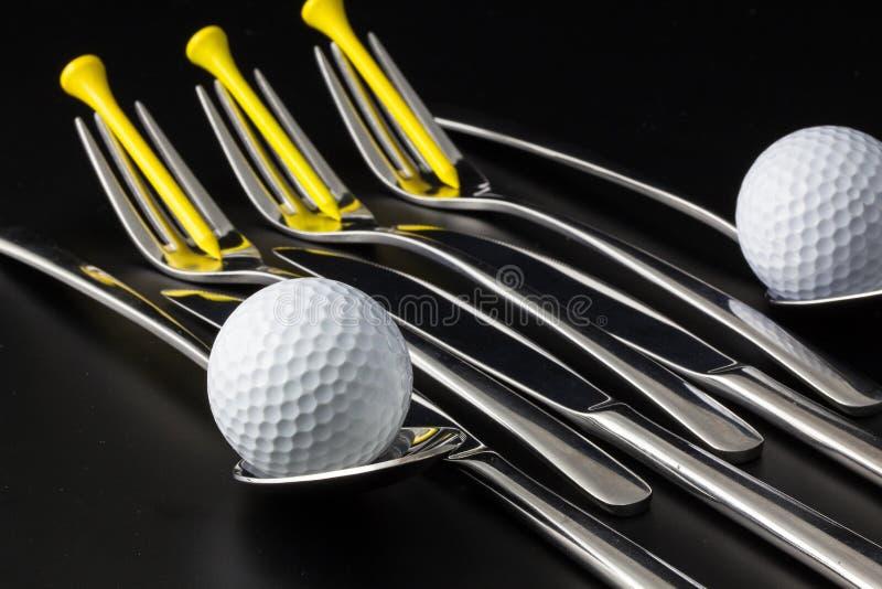 Gabeln, Löffel und Messer und Golfbälle stockbilder