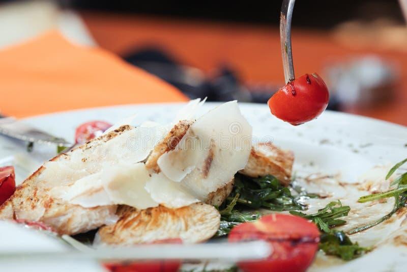 Gabeln Sie mit geschmackvoller gegrillter Hühnerleiste mit heitren Tomaten - gesundes Leben lizenzfreie stockbilder