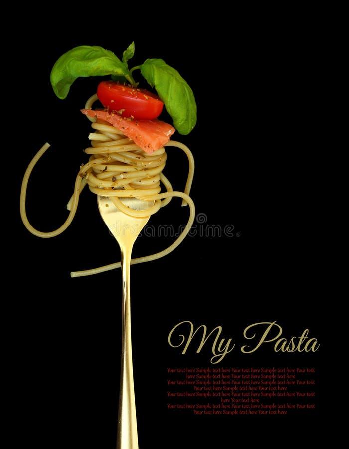 Gabeln Sie mit Spaghettis, Tomate, Lachsen und Basilikum stockfotografie