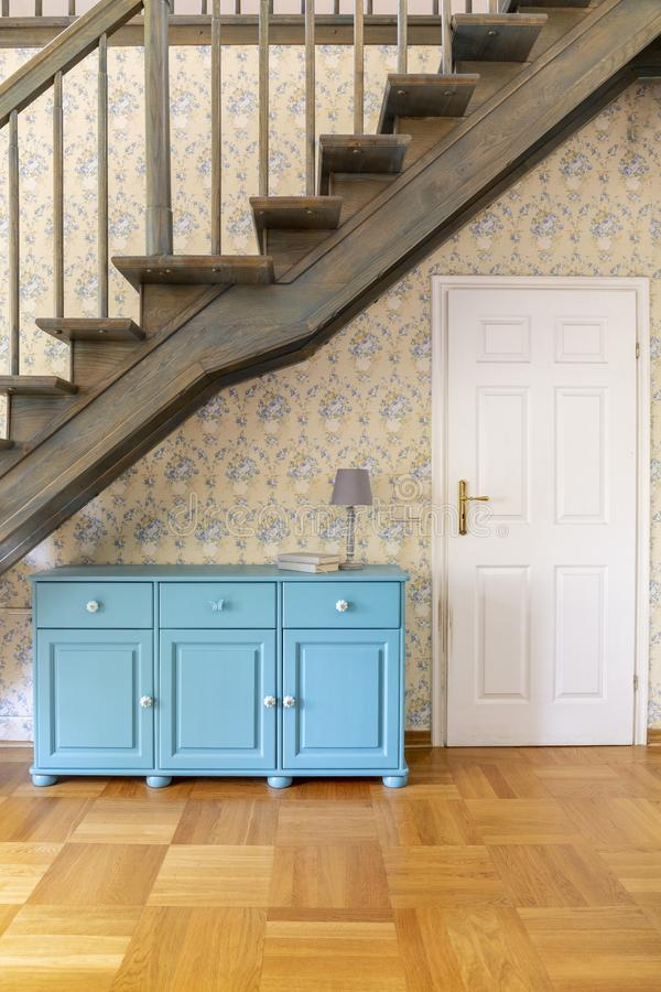 Gabinete azul con la lámpara al lado de la puerta blanca en el pasillo de la casa con imagen de archivo libre de regalías