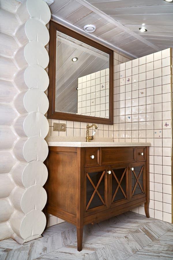 Gabinete de la vanidad del cuarto de baño con la encimera de acrílico y marco de madera del espejo en cuarto de baño de lujo Esti fotografía de archivo