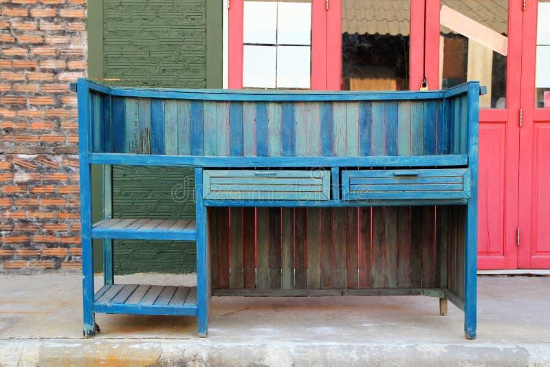 Gabinete de madera azul del vintage en un fondo de la pared de ladrillo y de puertas de madera imagen de archivo libre de regalías