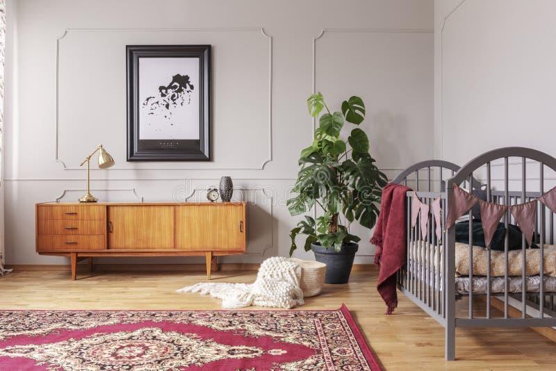 Gabinete de madera retro en interior gris del dormitorio del bebé con la planta del monstruo en el pote negro y el pesebre de mad imagenes de archivo
