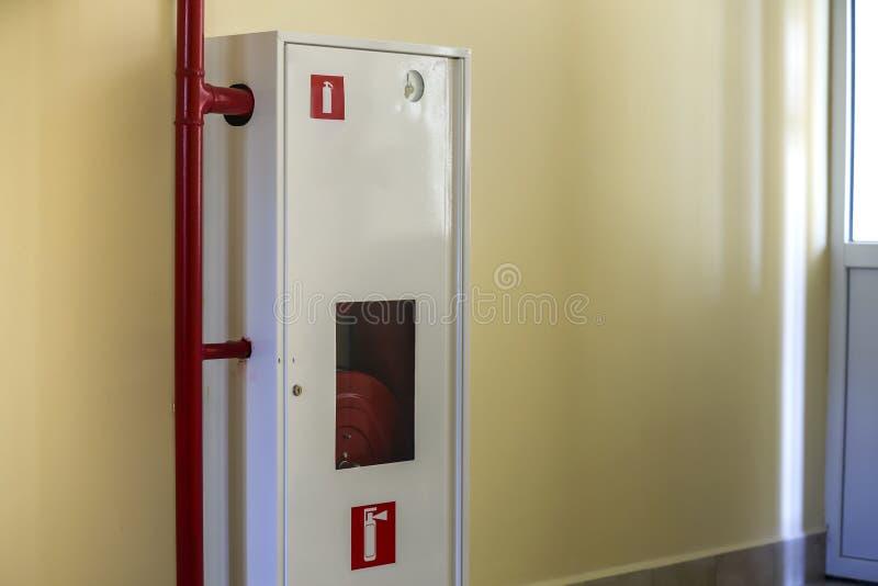 Gabinete del metal blanco con el carrete extintor de la manguera en fondo ligero del espacio de la copia de la pared imagenes de archivo