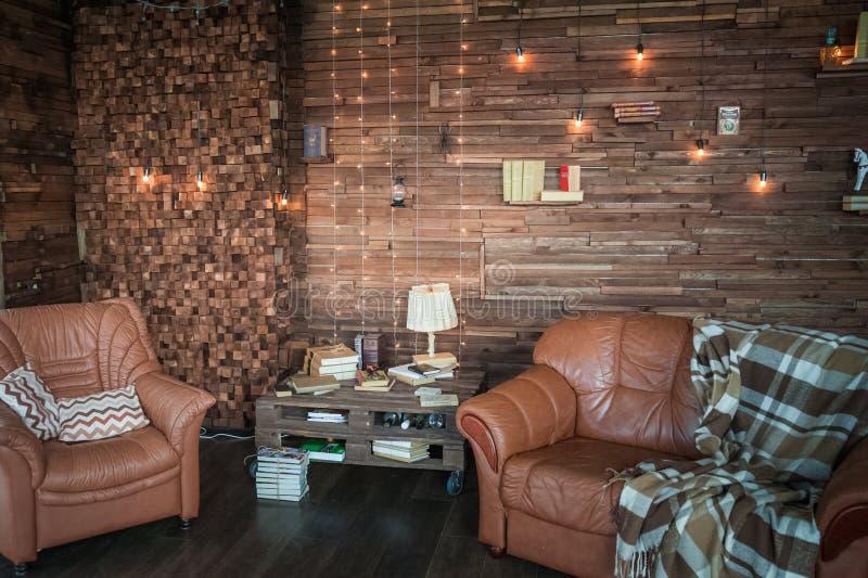 Gabinete en el estilo del desván Sala de estar en ekostyle Sofás de Brown, libros y haces de madera imagen de archivo libre de regalías