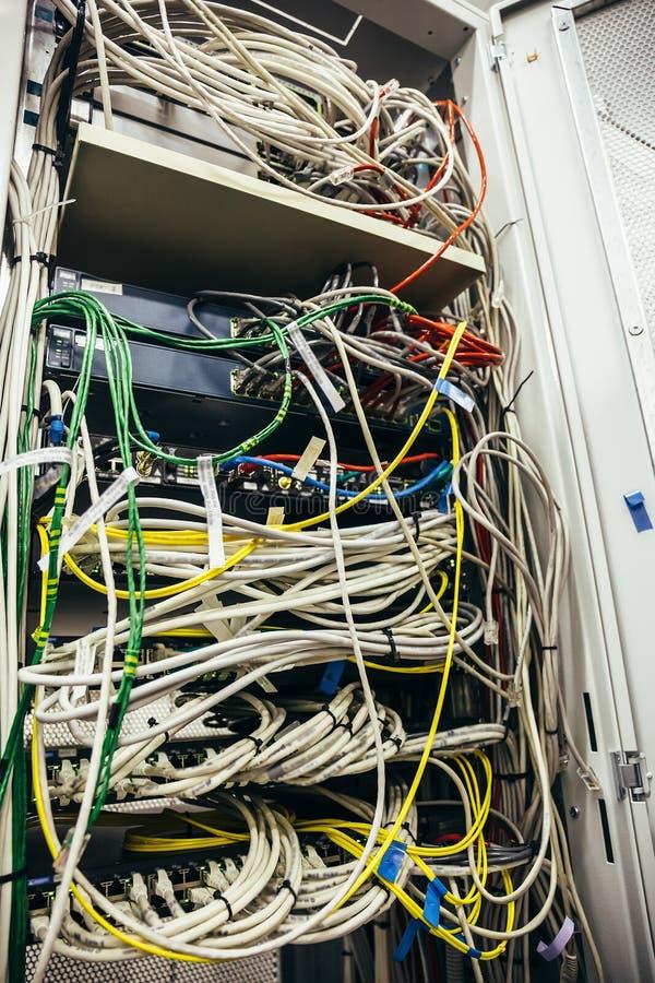 Gabinete interior con la centralita telefónica y el otro equipo móvil del hardware de la red de la telecomunicación con muchos ca fotografía de archivo libre de regalías
