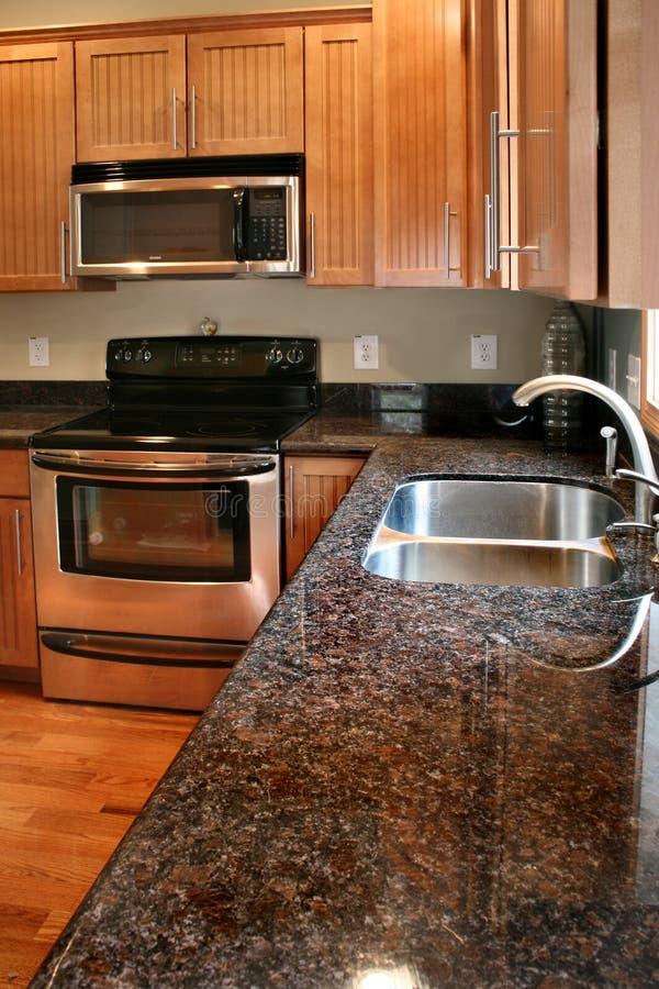 Gabinetes de madeira da cozinha pretos e fogão inoxidável foto de stock royalty free