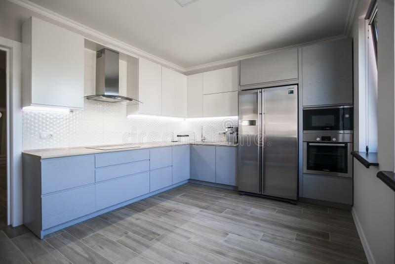Gabinetti blu e bianchi nell'interno moderno della cucina fotografia stock
