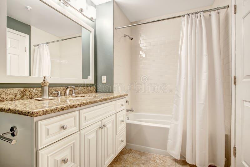 Gabinetto bianco di vanità del bagno con la cima del granito e bianco bianco b immagini stock