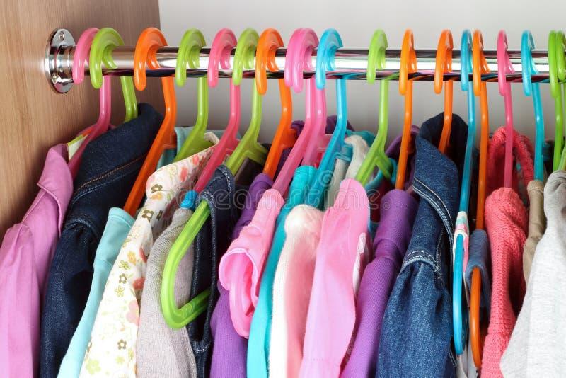 Gabinetto con i vestiti dal bambino sui ganci immagine stock libera da diritti
