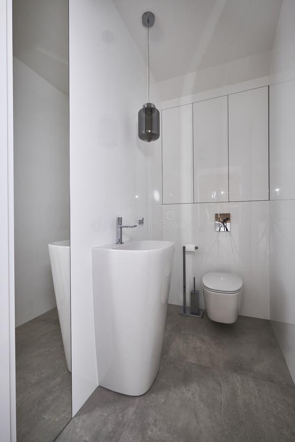 Gabinetto moderno con il miror e le pareti bianche immagini stock libere da diritti