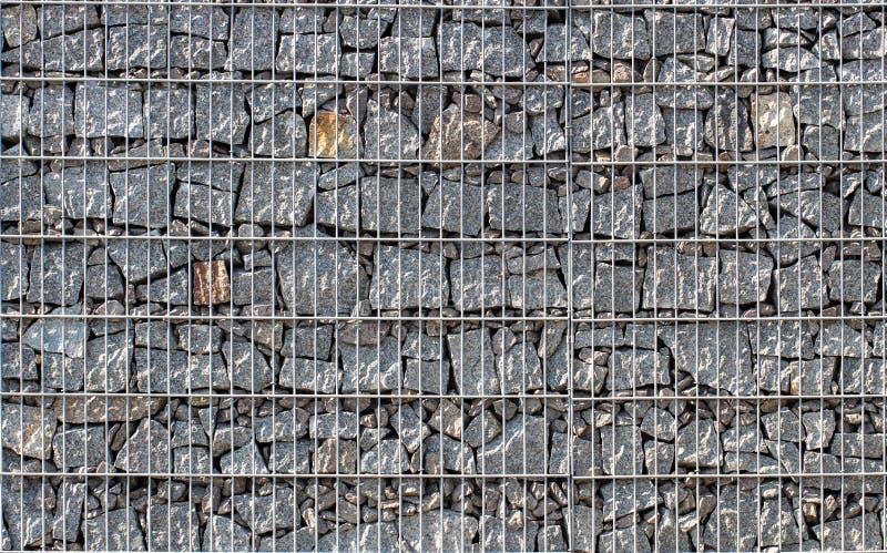 Gabion, ένας τοίχος πετρών με ένα πλέγμα μετάλλων της γκρίζας σύστασης γρανίτη στοκ εικόνα