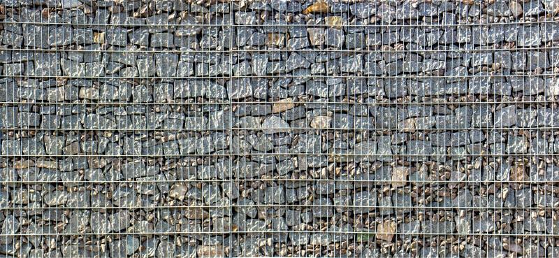 Gabion, ένας τοίχος πετρών με ένα πλέγμα μετάλλων της γκρίζας σύστασης γρανίτη στοκ φωτογραφία
