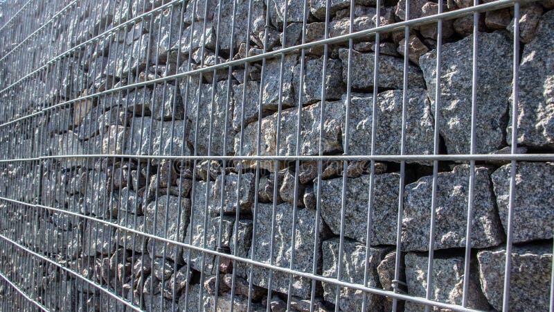 Gabion, ένας τοίχος πετρών με ένα πλέγμα μετάλλων της γκρίζας σύστασης γρανίτη στοκ εικόνες
